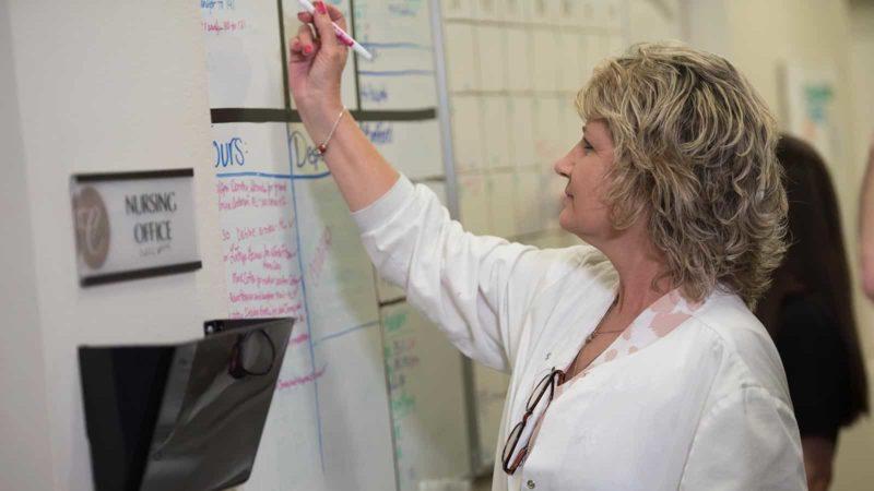 Nurse writing on board in memory care nursing office