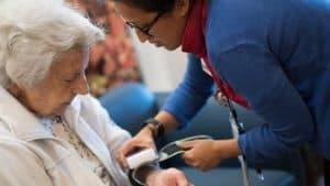 Nurse putting blood pressure monitor on senior woman