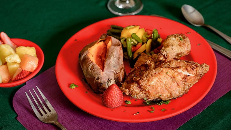 Fried chicken and vegetables on red plate
