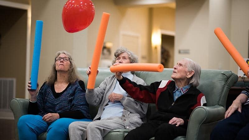 Group seniors playing balloon noodle game