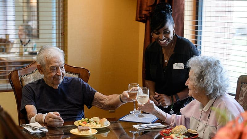 Senior couple dining in private with staff waiter