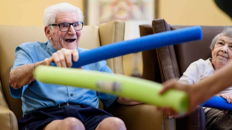 Senior man holding foam pool noodle during memory care game