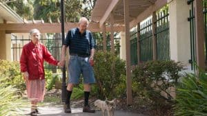Senior man and woman holding hands and walking on secure landscaped path in memory care community