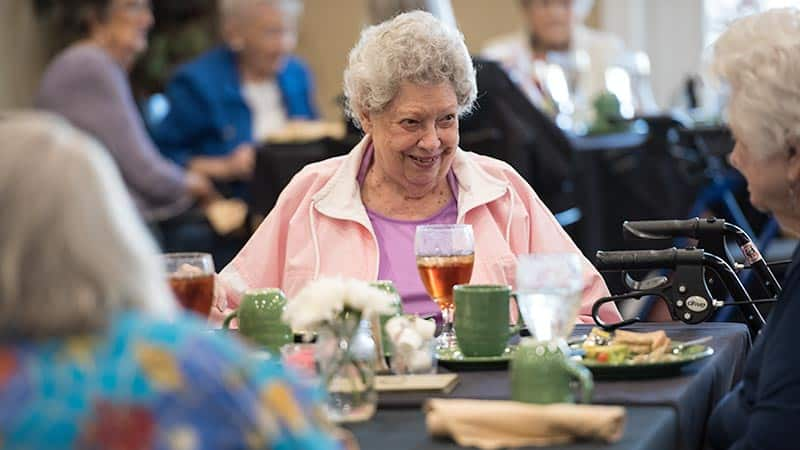 Senior woman seated at table smiling