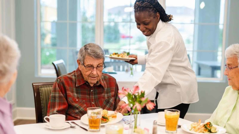 Dining staff serving meal to senior man seated at dining room table in memory care community