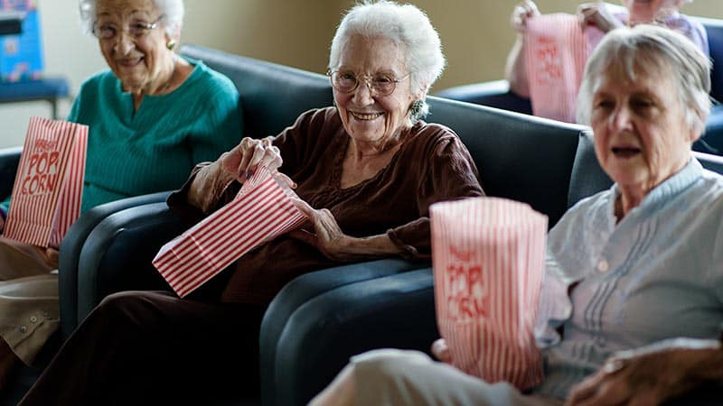 Three senior women watching a movie with popcorn