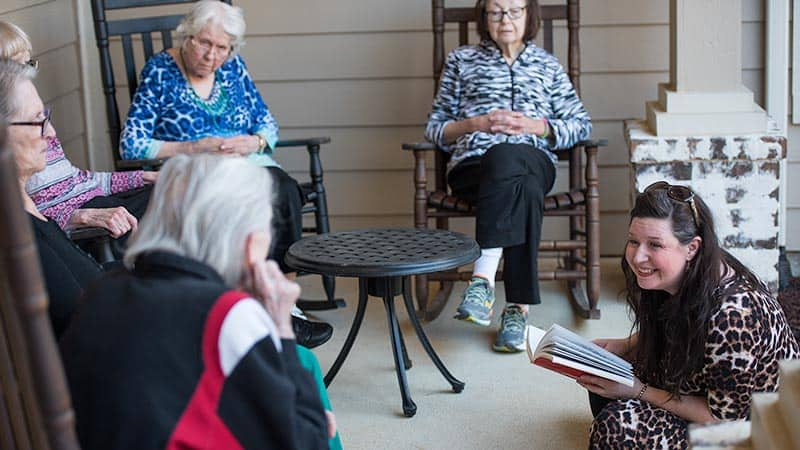 Woman reading to group of senior women